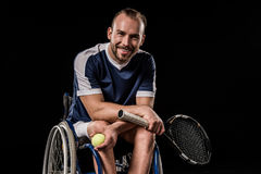 Young man in sportswear sitting in wheelchair and holding tennis racquet with ball Stock Images