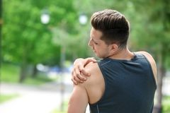 Young man in sportswear suffering from shoulder pain outdoors. Man in sportswear suffering from shoulder pain outdoors royalty free stock image