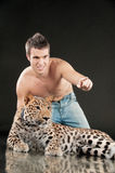 Young man and spotty leopard stock photography