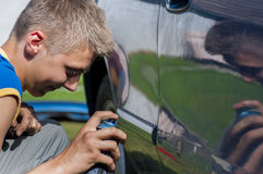 Young man spraying a car. Royalty Free Stock Photography