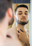 Young man spraying fragrance perfume Royalty Free Stock Image