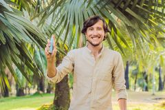 Young man spraying mosquito insect repellent in the forrest, insect protection stock image