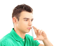 Young man spraying nose drops Royalty Free Stock Photos