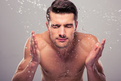 Young man spraying water on his face. Over gray background Stock Images