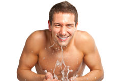 Young man spraying water on his face after shaving in the bathroom Royalty Free Stock Photo