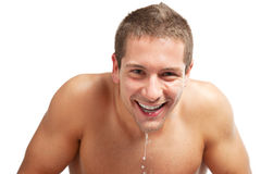 Young man spraying water on his face after shaving in the bathroom. Young man splashing water on his face Royalty Free Stock Photography