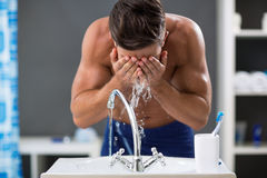 Young man spraying water on his face after shaving Stock Images