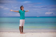 Young man spread his arms standing on white sandy Royalty Free Stock Photos