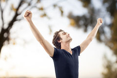 Young man spreading arms in nature Stock Image