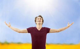 Young man spreading arms in nature Stock Photos