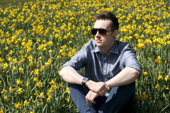 Young man in spring scene with daffodils Stock Image