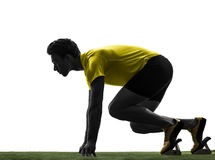 Young man sprinter runner in starting blocks silhouette. One caucasian man young sprinter runner  in starting blocks  silhouette studio  on white background Stock Photos
