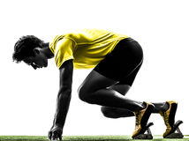 Young man sprinter runner in starting blocks silhouette. One caucasian man young sprinter runner  in starting blocks  silhouette studio  on white background Royalty Free Stock Photography