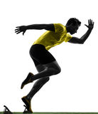 Young man sprinter runner in starting blocks silhouette Royalty Free Stock Image