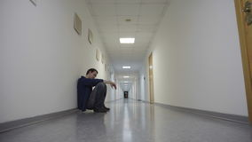 Young man squats leaning to wall in long corridor and waiting stock footage