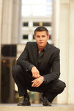 Young man squatting Stock Photos