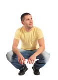 Young man in squatting position Royalty Free Stock Images