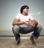 Young man squatting on the sand Stock Photos