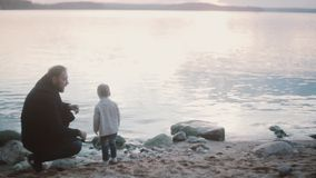 Young man squatting on a shore and talking with little boy, than stand up. Father and son spending time together. stock video footage