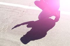 Young man squatting with a smartphone and a shadow of it on the pavement. royalty free stock photography