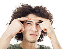 Young man squeezes a pimple on him forehead. Teenager squeezes a pimple on him forehead stock photography