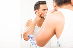 Young man squeezing a pimple. Good looking young man standing close to a mirror in the bathroom and squeezing a pimple on his face stock image