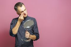 Young man squeezing pimple looking into mirror. Isolated on pink background. Acne. Skin care. royalty free stock image
