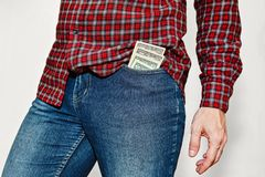 Young man with stack of dollars in pocket. Young male person in classic checkered shirt and blue jeans pants with a stack of US dollars currency in front pocket Royalty Free Stock Photos