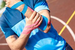 Young man on stadium outside standing wearing kinesio tape around elbow close-up royalty free stock photos