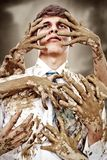 Stained soul. Young man stained by multitude of dirty hands Stock Image