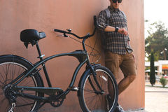 Young Man Stand Near Bicycle On Wall Background And Looks At His Watch. A handsome young man in sunglasses stands next to a bicycle on the background of a Royalty Free Stock Photo