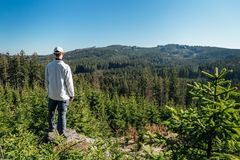 Young man stand on rock with forest and blue sky, looking to valley.  stock images