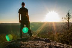 Young man stand on rock with forest and pond, looking to valley.  royalty free stock photo