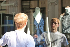 Young man standing above a shop show-window. Royalty Free Stock Images