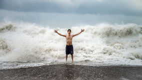 Young man standing against the sea waves with splash in a cloudy storm weather. Antalya - Turkey - October 17, 2013: Young man standing against the sea waves Royalty Free Stock Photos