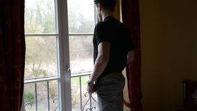 Young man standing against window, sad or worried, thinking stock video footage