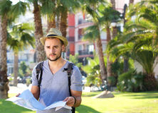 Young man standing alone outside with backpack and map Royalty Free Stock Photography