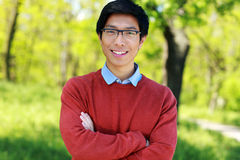 Young man standing with arms folded in a park Royalty Free Stock Photography