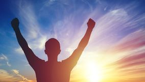 Young man standing with arms outstretched at sunset royalty free stock images