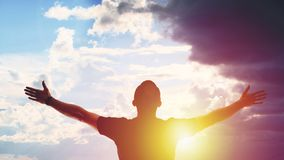 Young man standing with arms outstretched at sunset stock image