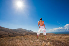 Young man standing back in mountains Royalty Free Stock Images