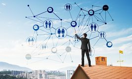 Businessman on house roof presenting networking and connection concept. Mixed media Stock Photo