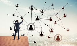 Businessman on house roof presenting networking and connection c Stock Images