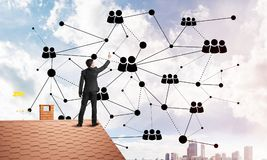 Businessman on house roof presenting networking and connection concept. Mixed media. Young man standing with back on roof and drawing connection lines. Mixed Stock Photo