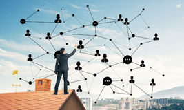 Businessman on house roof presenting networking and connection c Stock Image