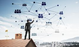Businessman on house roof presenting networking and connection c Stock Photos