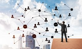 Businessman on house roof presenting networking and connection concept. Mixed media Stock Photos