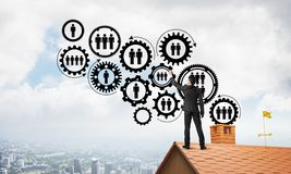 Businessman on house roof presenting teamwork and connection concept. Mixed media. Young man standing with back on roof and drawing gear teamwork concept. Mixed Royalty Free Stock Image