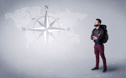 Young man standing with a backpack. Handsome young man standing with a backpack on his back and a compass and a world map in the background Royalty Free Stock Image