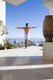 Young man standing on balcony, arms outstretched, rear view Royalty Free Stock Photos